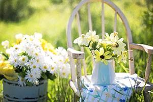 Bild på en stol med en vas med sommarblommor på.