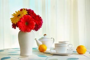 Bild på en bordsmiljö med blomvas, kaffeservis och apelsiner.